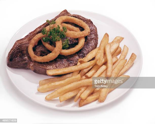 View of a grilled steak with french fries and onion rings on a white plate against a white background 1990