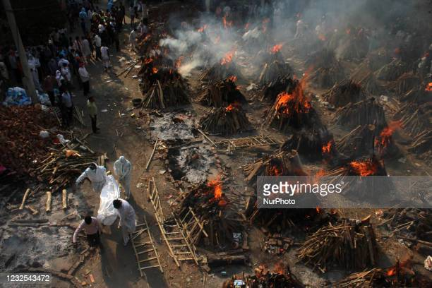 View of a ground showing funeral pyres during a mass cremation of victims, who died due to the coronavirus disease, at a crematorium in New Delhi on...