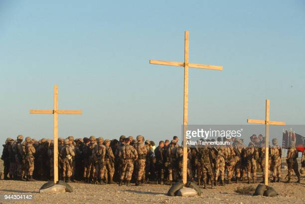 View of a group of American soldiers behind a trio of crosses as they participate in a religious service during the Gulf War Iraq 1991