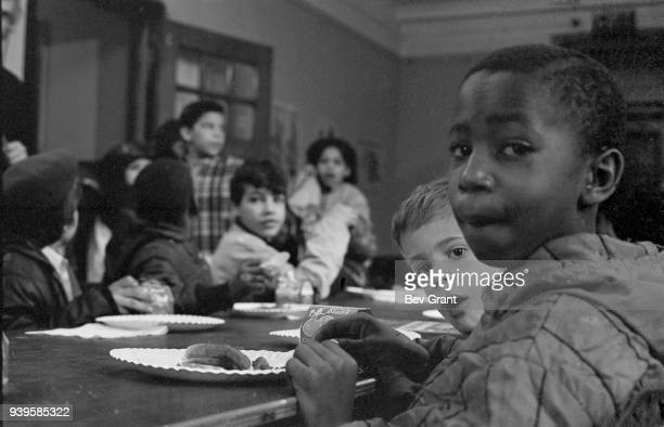 View of a group of boys as they eat during a free breakfast for children program sponsored by the Black Panther Party, New York, New York, winter...
