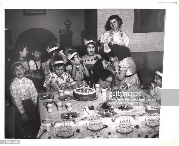 View of a group of children posed behind a cake on a table at a birthday party 1940s Most of them wear feathered headbands Photo by Weegee...