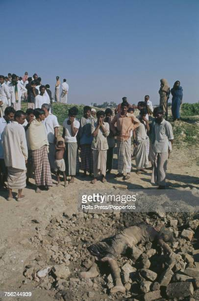 View of a group of civilians looking at a dead body in a brickyard on the outskirts of Dhaka in East Pakistan on 18th December 1971 The body is one...