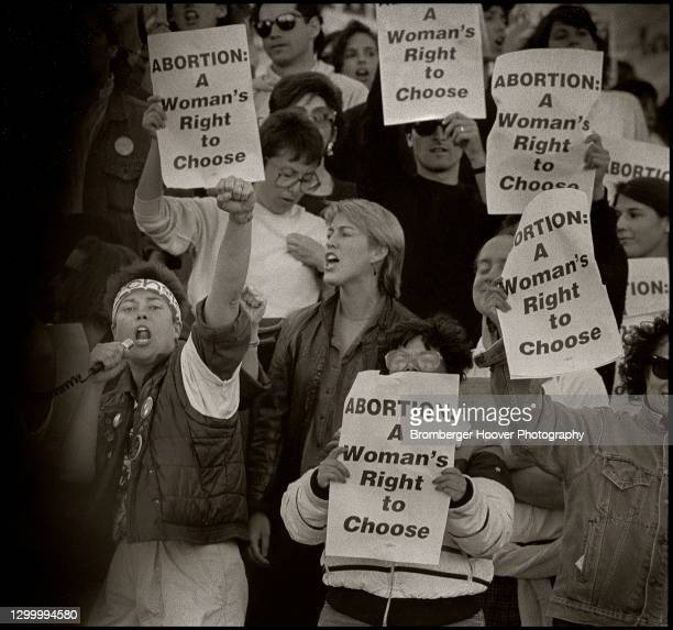 View of a group of demonstrators, many with signs, during a pro-choice rally, San Francisco, California, 1989. The signs read 'Abortion: A Woman's...
