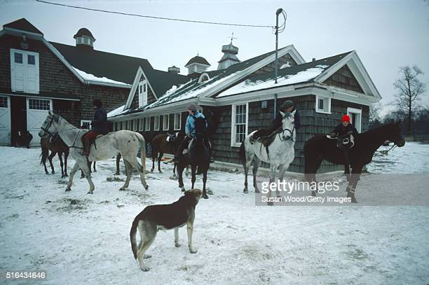 View of a group of horse riders on the snowy grounds outside Harry de Leyer's Long Island farm house Smithtown New York 1976 De Leyer famously...