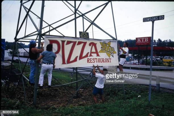 View of a group of men as they affix a restaurant sign to the base of a roadside pylon during the Woodstock '94 festival, Saugerties, New York,...