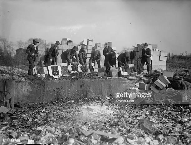 View of a group of men as they destroy bottles of whiskey beer during Prohibition November 20 1923