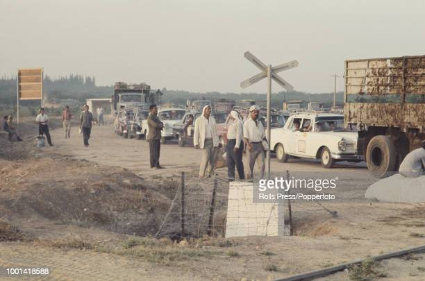 View of a group of Palestinian men watching cars trucks and taxis queuing at an Israeli checkpoint on the border between Israel and the Israeli...
