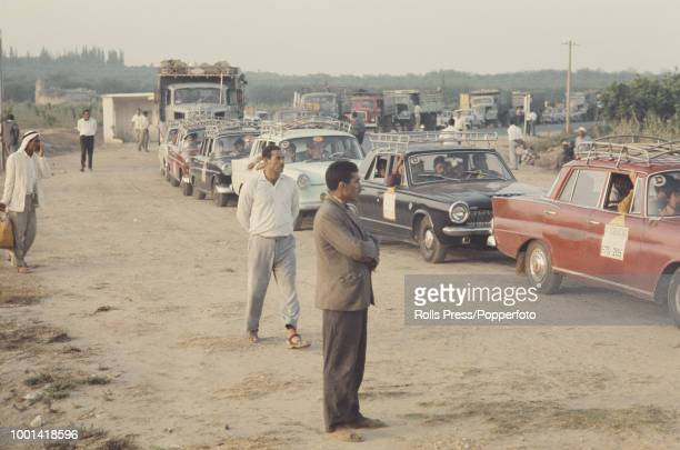 View of a group of Palestinian men watching cars trucks and taxis queuing at an Israeli checkpoint as they wait to cross the border between Israel...