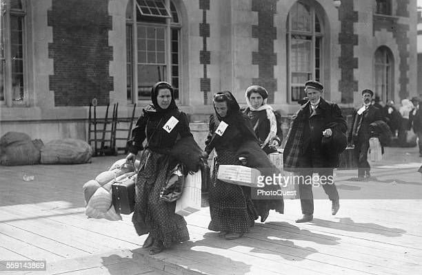View of a group of recently arrived immigrants as they carry their belongings at Ellis Island, New York, New York, early 1900s.