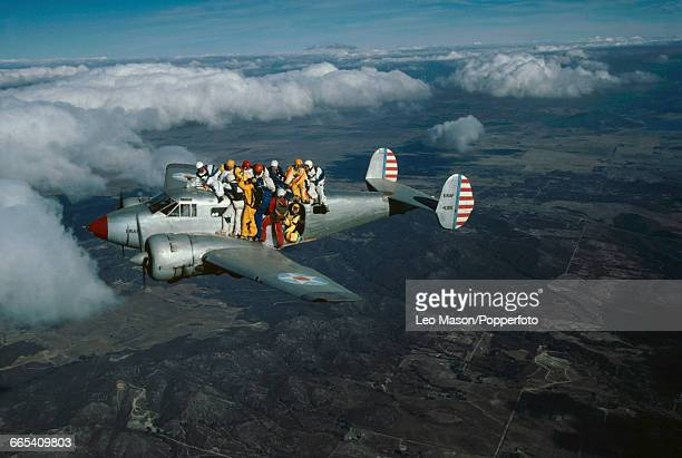 View of a group of skydivers holding on to the exterior of an aeroplane as they prepare to skydive in formation before activating their parachutes...