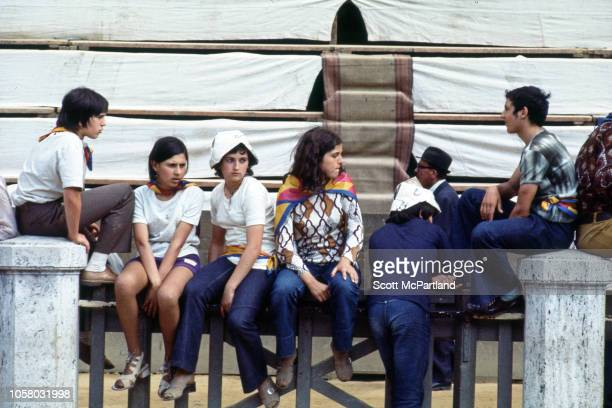 View of a group of teenagers as they sit on a fence in Piazza del Campo during the Palio Di Siena horse race Siena Italy August 16 1968 The...