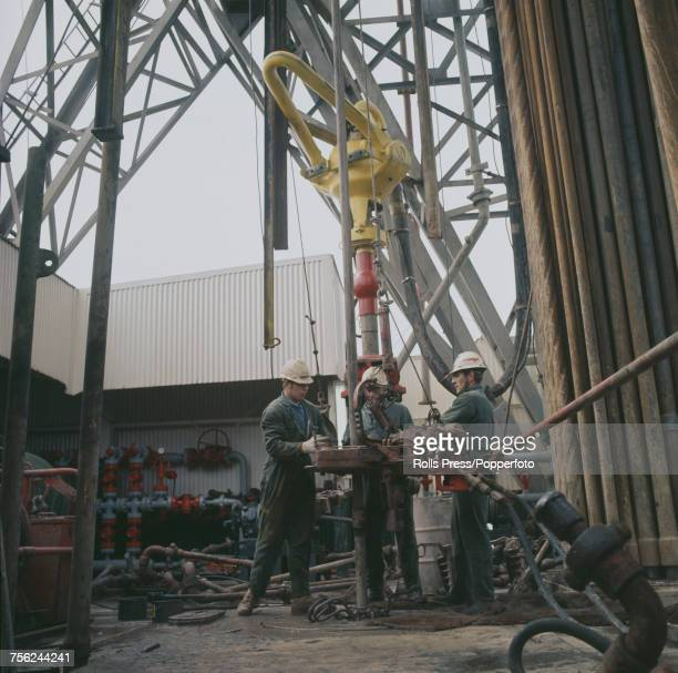 View of a group of three oil rig workers attending to the rotary table above the drill floor as they work on a Phillips Petroleum offshore drilling...