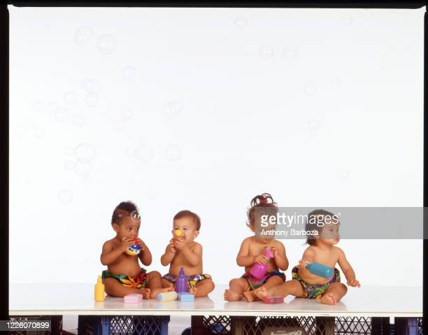 View of a group of unidentified babies, posed against a white background, as they play with bubble toys, New York, New York, 1990s