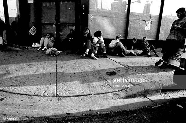 View of a group of unidentified teenagers as they sit on a sidewalk near the intersection of Belmont and Clark streets Chicago Illinois 1996