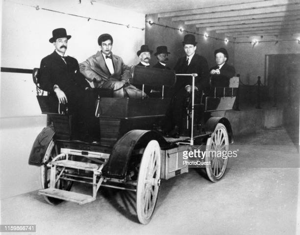 View of a group of unidentified US Senators and staff members as they sit in an electric Studebaker car in the tunnel that links the Russell Senate...