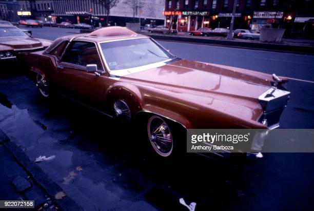 View of a heavily customized 1973 Lincoln Continental 'pimpmobile' parked on Seventh Avenue at West 124th Street New York New York 1970s