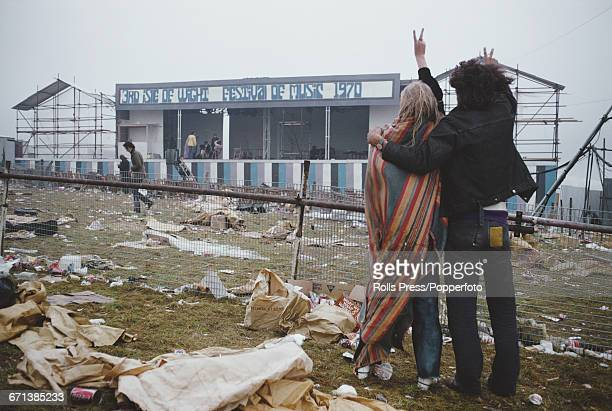 View of a hippy couple and festival goers making the peace sign as they stand amongst discarded rubbish and look towards the empty stage at the end...