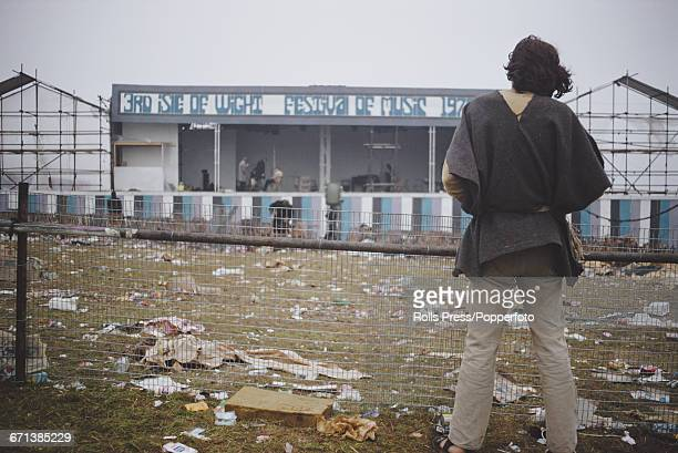 View of a hippy festival goer standing amongst discarded rubbish as he looks towards the empty stage at the end of the Isle of Wight Festival 1970...