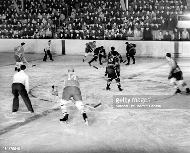 View of a hockey game between the Shawinigan Cataracts, in light uniforms, and the Montreal Royals held at the municipal arena of Shawinigan, Quebec,...