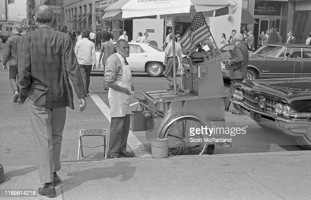 View of a hot dog vendor as he stands with his cart at the intersection of Murray Street and Broadway in Tribeca New York New York September 21 1970...