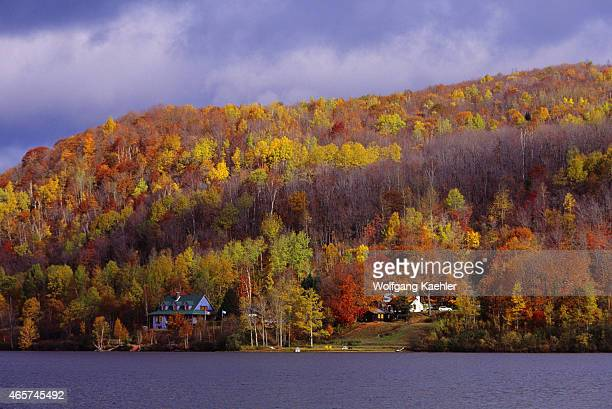 View of a house at Lake Lac Mercier near MontTremblant National Park in the Laurentians Quebec Province Canada with tree covered hillside in fall...