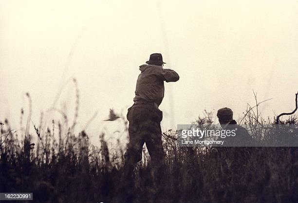 View of a hunter Peter Salm as he stands to take a shot while hunting in Denmark 1995 An unidentified man crouches next to him