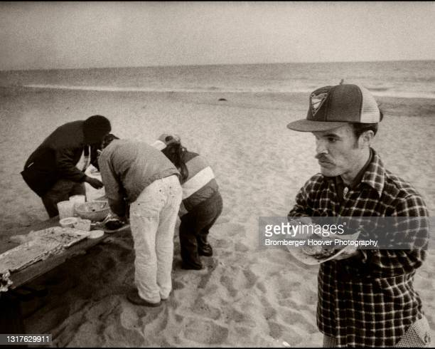 View of a Jim Cady as he holds a plate of food near a picnic table on the beach, Los Angeles, California, 1982. Behind him, three other people served...