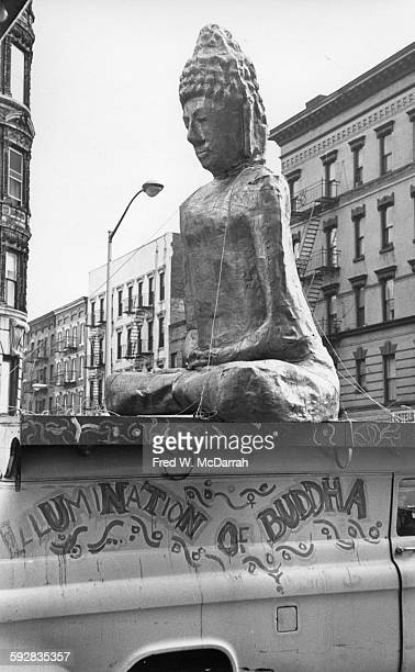 View of a large Buddha statue on top of a van that advertises Dr Timothy Leary's multimedia presentation 'Illumination of the Buddha' at the Village...