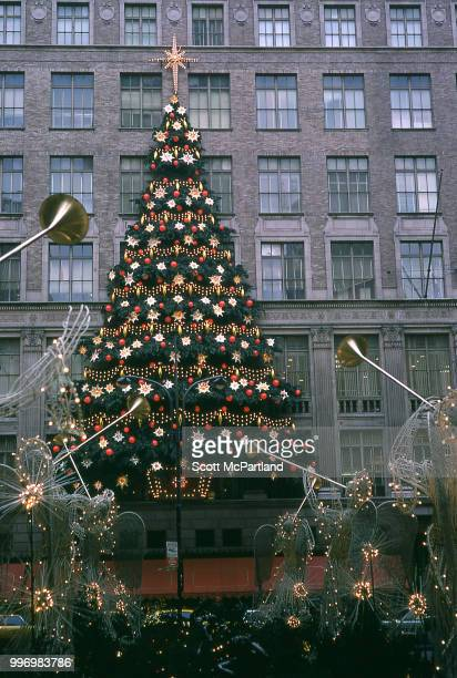 View of a large Christmas tree as seen through angel statues adorned with Christmas lights on the promenade at Rockefeller Center in midtown...
