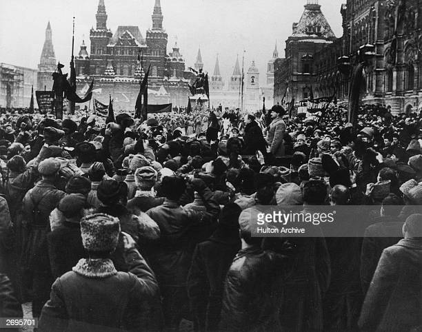 View of a large crowd assembled in Red Square with Bolshevik leaders Joseph Stalin and Leon Trotsky standing on a podium during the Russian...