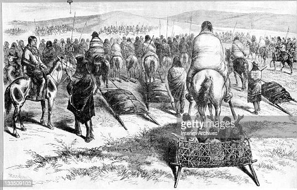 View of a large group of Native American Sioux as they ride on horseback some with travois and others on foot on their way from Camp Sheridan to...