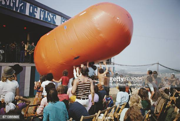 View of a large lozenge shaped orange inflatable being manhandled by audience members as a band plays on stage at the Isle of Wight Festival 1970 in...