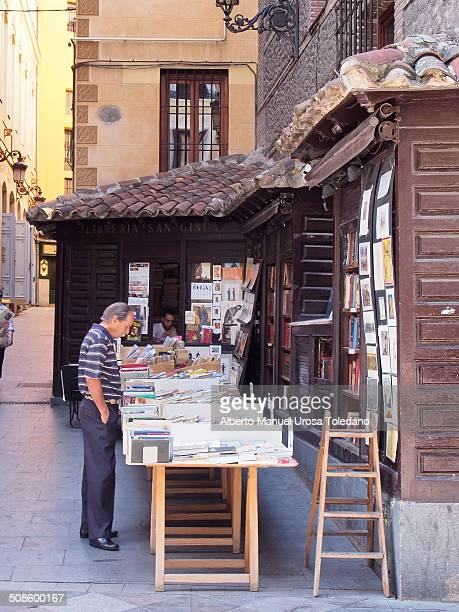 A view of a library located in the street where old books are placed in tables and people can buy or trade with them This photo show a customer the...