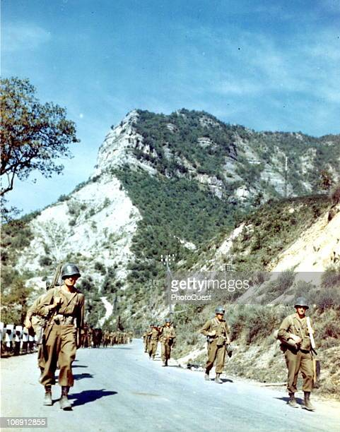 View of a line of American infantrymen of the 88th Division march along a picturesque mountain road that leads to Bologna Italy mid to late 1944