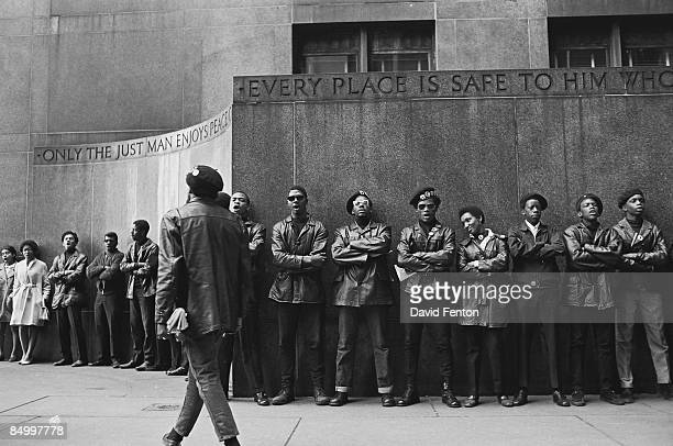 View of a line of Black Panther Party members as they demonstrate, under a pair of engraved quotes, outside the New York County Criminal Court , New...