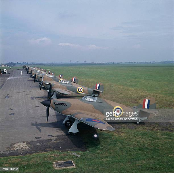 View of a line of Hawker Hurricane single seat fighter aircraft along with the odd Supermarine Spitfire fighter aircraft being prepared for use in...