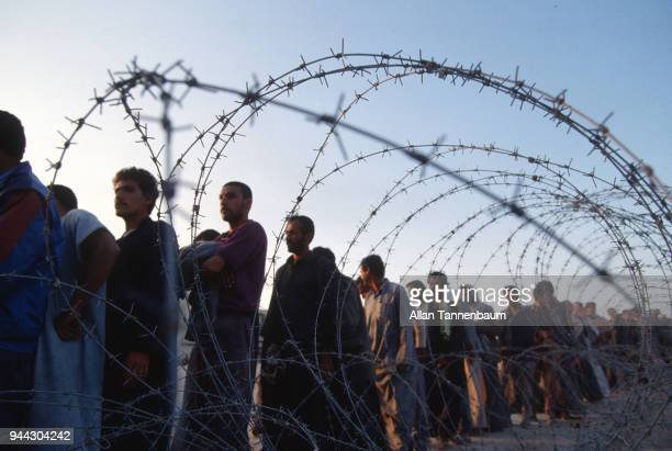 View of a line of Iraqi men as seen through a barbed wire fence at a refugee camp during the Gulf War Iraq 1991