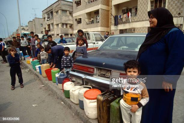 View of a line of Palestinians as they wait with plastic buckets and cans for water distribution during the Gulf War Kuwait City Kuwait 1991