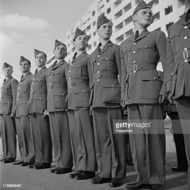 View of a line of Royal Air Force pilots, having arrived from all parts of the Empire, standing to attention during basic training in front of Marine...
