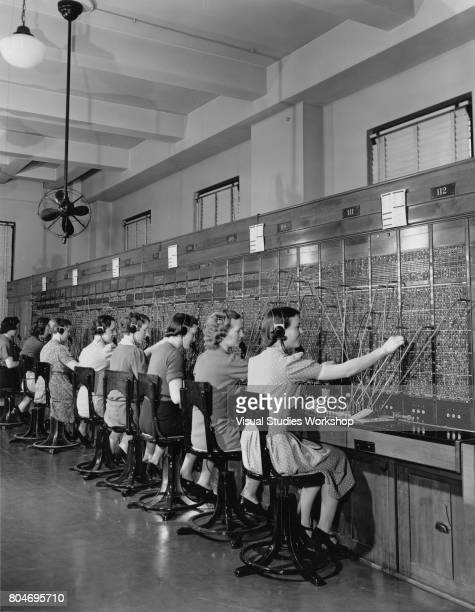View of a line of women as they work at a switchboard circa 1930
