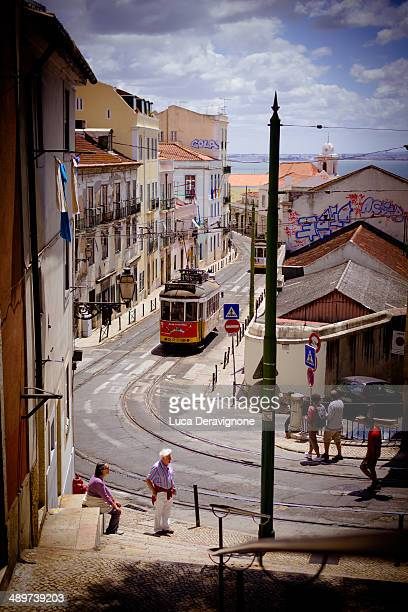 CONTENT] A view of a Lisbon street with tram line and tourists