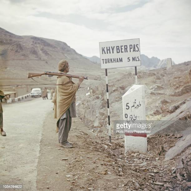 View of a local armed tribesman standing beside a signpost on the Khyber Pass mountain road in the north west frontier area of Pakistan near the...