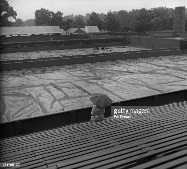 A view of a lone spectator holding an umbrella against the rain looks upon the covered court as the bad weather stops play on 25 June 1954 at the All...
