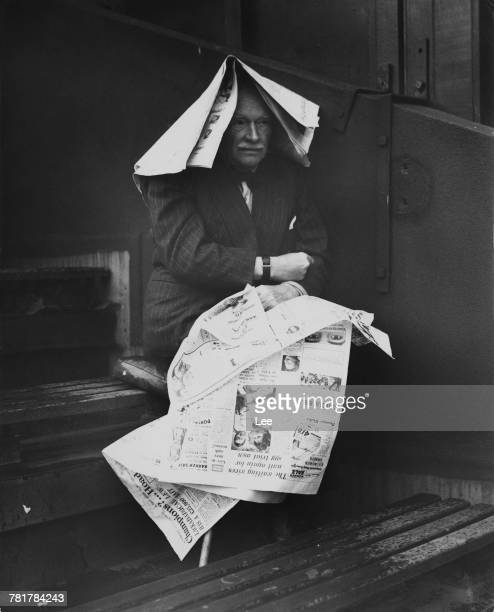 A view of a lone spectator using newspapers to shield against the rain looks out the covered court as the bad weather stops play on 24 June 1957 at...