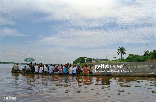 View of a long wooden dugout canoe crowded with people on the Congo River, Democratic Republic of the Congo, 2003. Photo taken during the National...