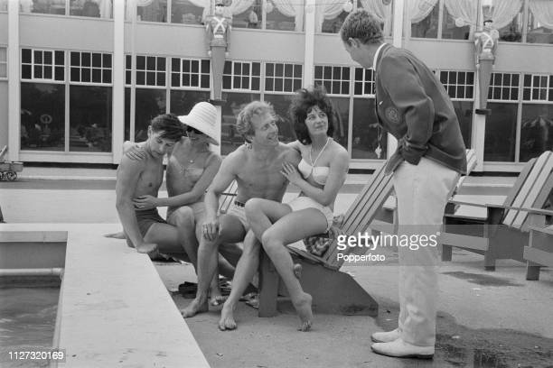 View of a male Butlins Redcoats staff member talking with two young couples wearing bathing costumes beside the swimming pool at Butlins Bognor Regis...