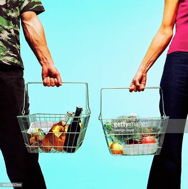 view of a man and a woman standing with goods in shopping baskets