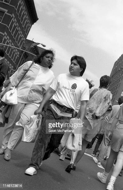 View of a man and woman as they walk on 9th Avenue in Hell's Kitchen during the International Food Festival New York New York May 14 1988