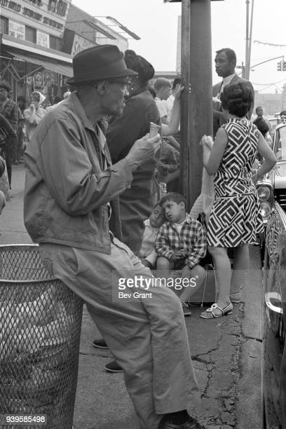 View of a man as he perches on the edge of a wire trash can and eats an ice cream cone at Coney Island Brooklyn New York New York July 4 1968