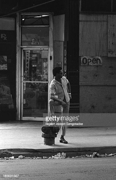 View of a man as he stands on a sidewalk, one leg up on a fire hydrant, Chicago, Illinois, mid 1960s.